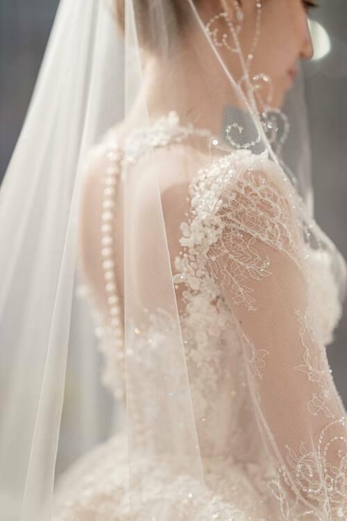 Cáchkết hợp giữa ngọc trai cùnghạt đá Swarovski trên tổng thể chiếc váy được ví như một sự giao thoa giữa phong cách thiết kế phương Đông và phương Tây, phù hợp với gu thời trang của cô dâu.