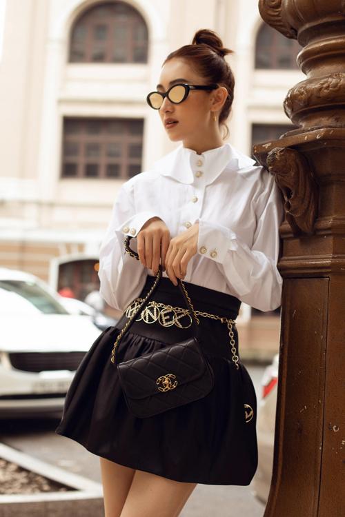 Hà Thu phối màu trắng đen hài hoà với áo blouse, chân váy chữ A dáng ngắn và các phụ kiện Chanel sang chảnh.