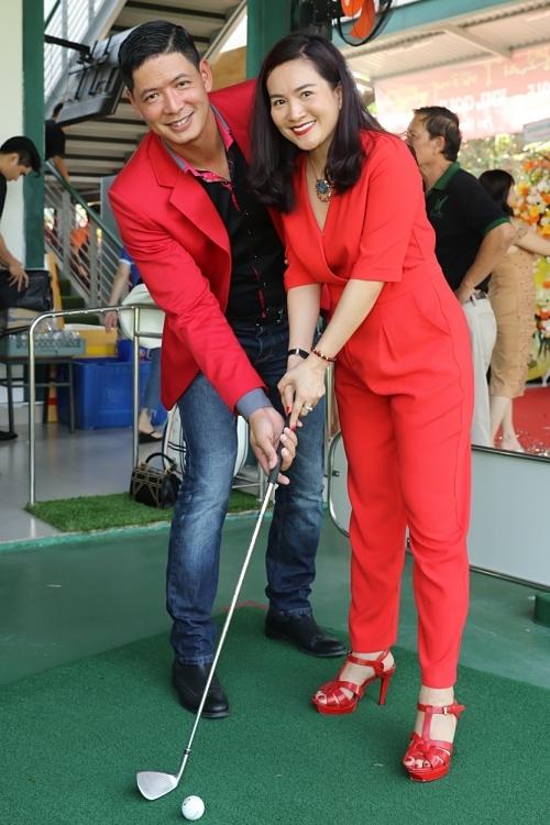 Bình Minh hướng dẫn vợ các động tác golf cơ bản. Đôi vợ chồng cũngchọn màu đỏ ton-sur-ton vì nó có ý nghĩa may mắn cho sự kiện quan trọng.