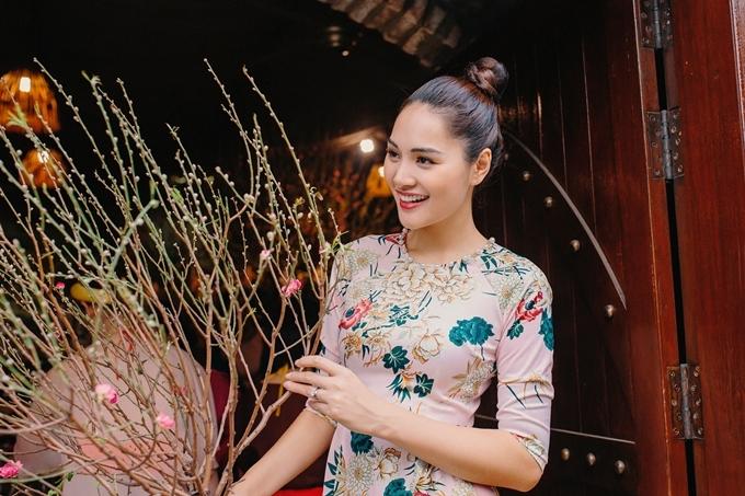 Hoa hậu Hương Giang thích thú ngắm cành đào được mang từ Nam Định vào.