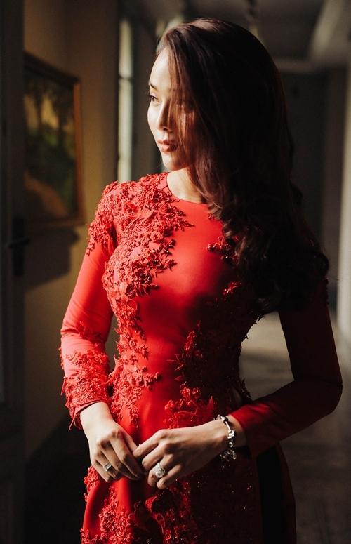 Bà xã Kim Cương chọn áo dài đính nổi các họa tiết trải dài từ ngực đến tà áo dài. Cô mang vẻ đẹp duyên dáng khi kết hợp cách trang điểm nhẹ nhàng, vòng tay đá.