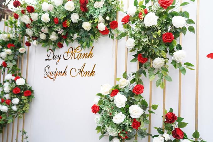 Khu vực photobooth trước nhà được tô điểm với hoa lụa hồng và tên của cặp cô dâu, chú rể9X.