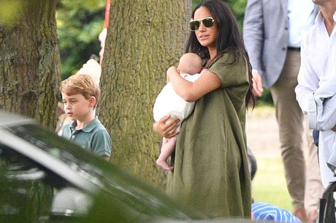 Meghan bế bé Archie 2 tháng tuổi, đứng gần Hoàng tử George khi đi cổ vũ chồng Harry trong trận đấu polo hồi tháng 7 năm ngoái. Ảnh: Rex.
