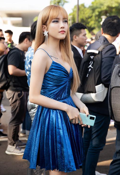 Cô mặc váy dây màu xanh coban khoe vai trần, ngực đầy gợi cảm.