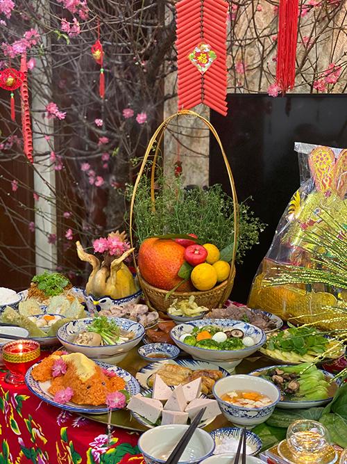 Khi làm cỗ, chị Nhung có thêm cô giúp việc làm phụ bếp. Chị sử dụng thêm khăn trải bàn hoạ tiết chim công, các loại hoa quả, cành đào để trang trí cho bữa cỗ.