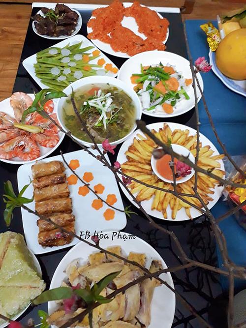 Các món ăn trong mâm cỗ của chị Hoà gồm có: xôi gấc cá chép, tôm hấp rượu, sườn nướng, mực xào cần tây, bánh chưng (mua sẵn), canh bò nấu dưa, khoai tây chiên, gà luộc, đậu luộc, nem ghẹ.