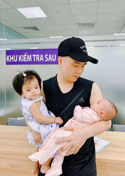 Nhà thiết kế Đỗ Mạnh Cường một nách bế hai con đi tiêm chủng. Anh hiện là ông bố của 6 người con nuôi.