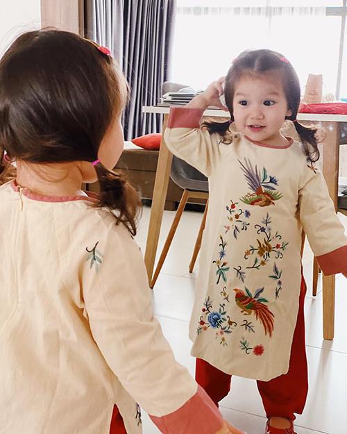 Bé Myla - con gái Hà Anh - thích thú ngắm mình trong gương khi diện áo dài xuân.