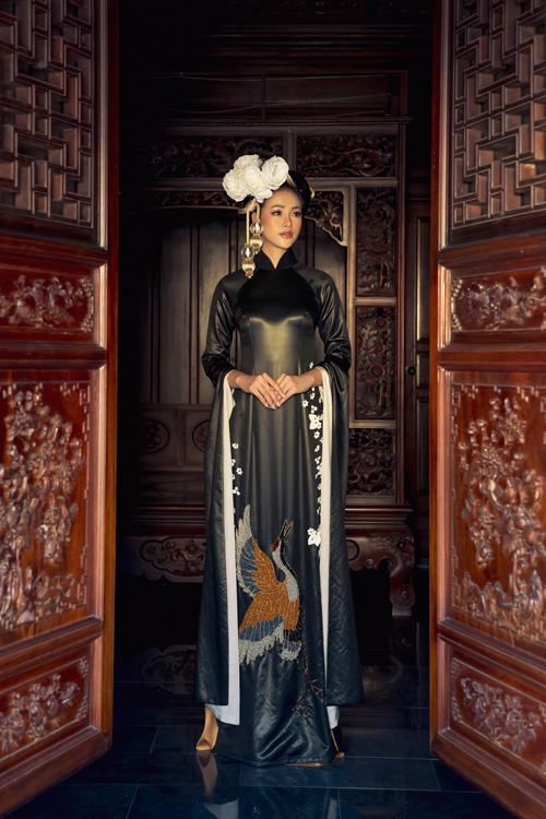 Trên nền chất liệu lãnh Mỹ A đen tuyền và bóng bẩy, nhà thiết kế chọn họa tiết cánh chim, hoa xuân để tô điểm cho áo dài.