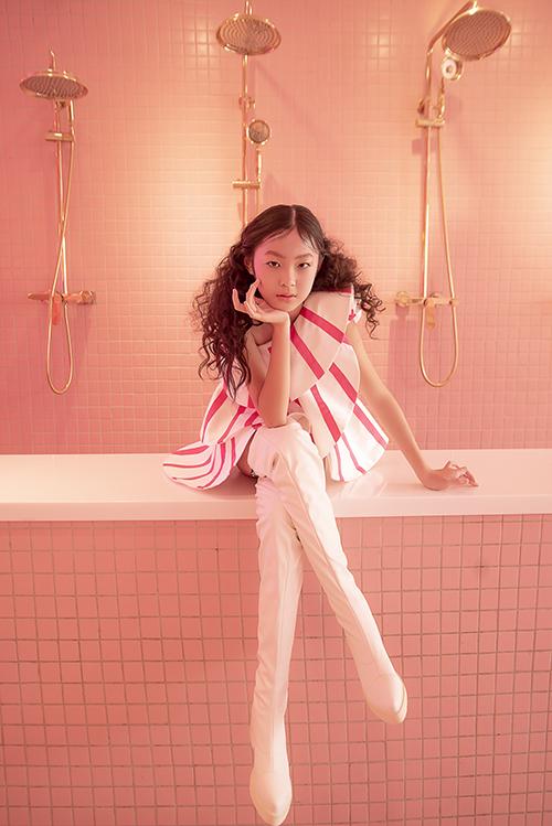 Đầm bất đối xứng với kiểu lệch vai được đưa vào dòng thời trang trẻ em một cách hài hoà. Phối cùng váy kẻ sọc trắng - hồng là kiểu bốt cao qua gối cá tính.