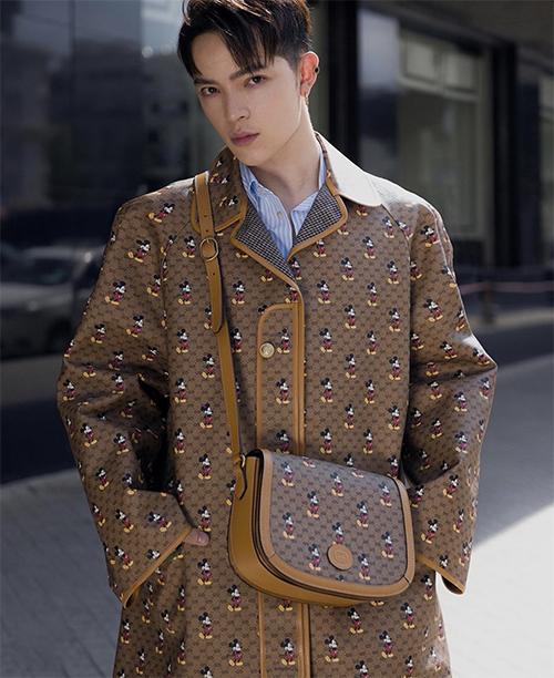 Stylist Kelbin Lei chọn áo choàng đồng điệu với túi đeo chéo trăng trí nhân vật hoạt hình nổi tiếng của hãng Disney.