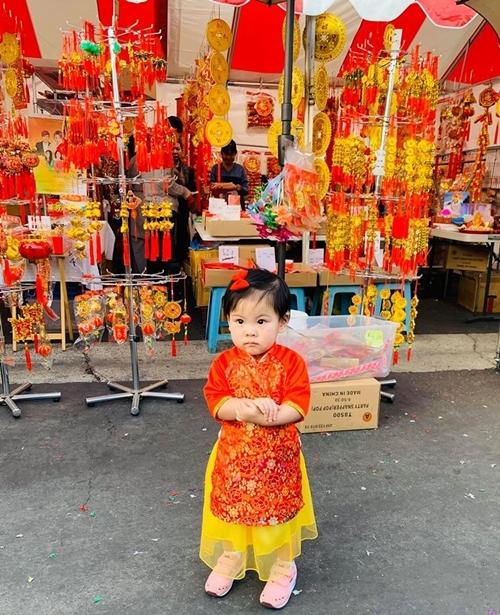 Bé Talia, con gái ca sĩ Thanh Thảo, xúng xính áo đỏ đi chợ Tết với mẹ.