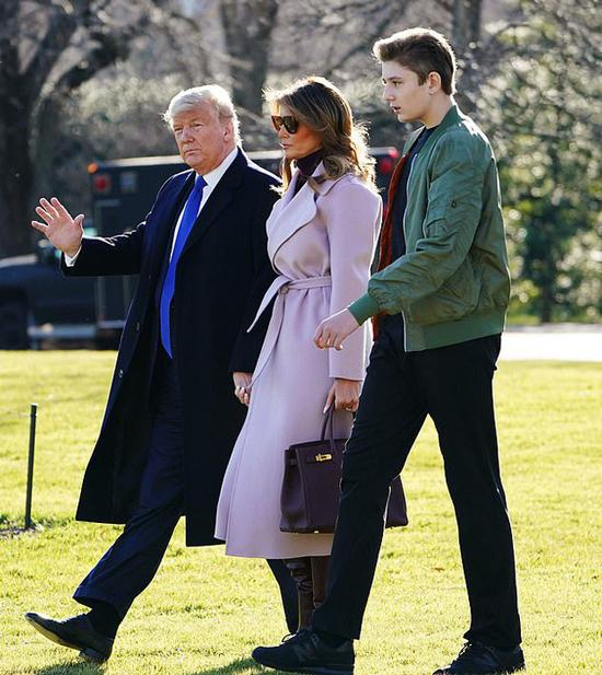 Tổng thống Mỹ nắm tay vợ và con trai đi bên cạnh khi di chuyển đến Floridachiều 17/1. Ảnh: AFP.