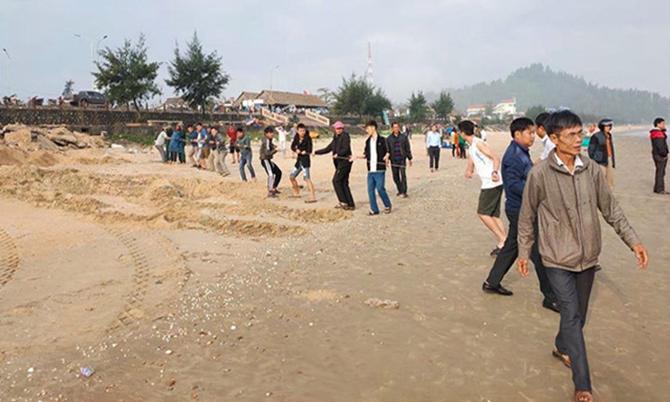 Người dân tập trung trên bờ biển Thiên Cầm theo dõi cứu hộ. Ảnh: H.L
