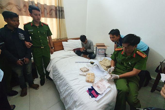 Hai thanh niên người Lào (thứ nhất và ba từ bên trái) cùng tang vật. Ảnh: Công an Quảng Trị