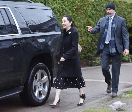 Bà Meng Wanzhou đi cùng nhân viên an ninh.