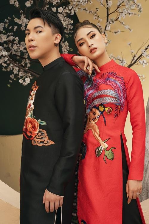 Kenbi Khánhmặc áo dài đen đối lập với bạn diễn. Họa tiếthọa tiết múa lân gợi không khí Tết và hàm ý mang đến lời chúc may mắn trong năm mới.