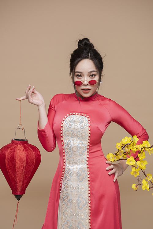 Bộ áo dài lụa đính kết trở nên sành điệu, trẻ trung hơn khi được nữ ca sĩ kết hợp với kính mátcùng tông.