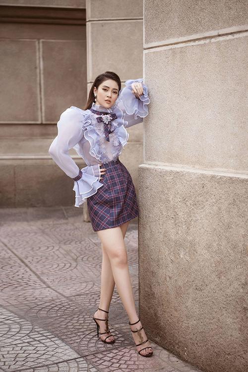 Lý Kim Thảo trông điệu đà, nữ tính khi diện thiết kế tay bồng kết hợp với bèo nhún ở cổ tay, dọc thân áo. Cô hoàn thiện vẻ ngoài bằng sandalscủa Yves Saint Laurent.