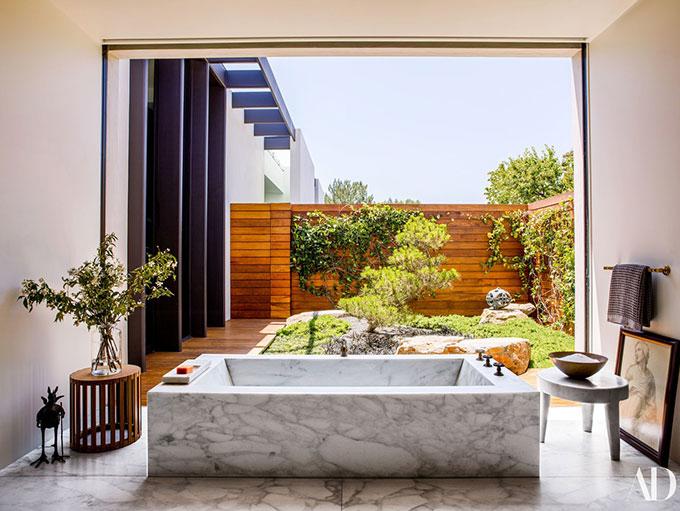 Phòng tắm lát đá cẩm thạch với cửa kính lớn đón ánh sáng tràn ngập.