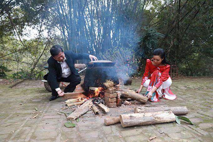 Nghệ sĩ Chiều Xuân diện áo dài xuân khi bắc bếp đun bánh chưng.