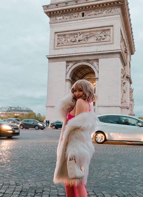 Ivy buông lơi áo khoác lông khoe vai trần, ngực đầy khi tạo dáng chụp ảnh trước công trình kiến trúc Khải Hoàn Môn nổi tiếng.