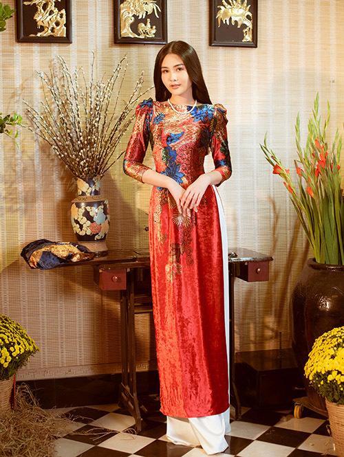 Hoa hậu duyên dáng với áo dài gam đỏ, cách điệu không cổ, tay bồng, hoạ tiết tinh tế.