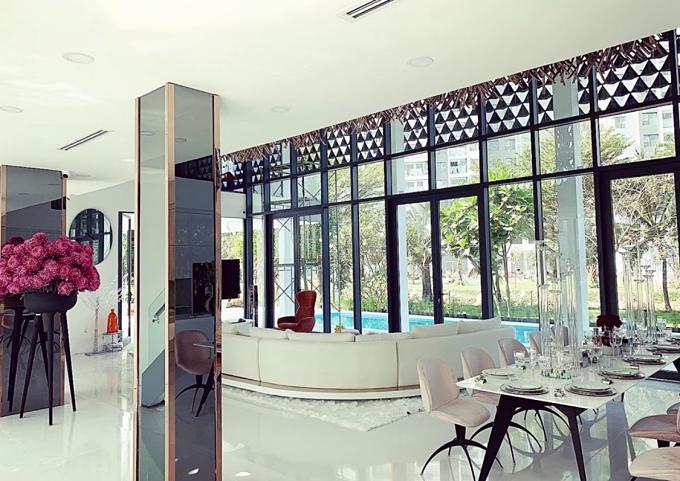 Phòng khách và bếp rộng khoảng 170m2, được nối liền nhau và có màu trắng - đên chủ đạo. Cô sử dụng thêm nhiều hoa tươi làm điểm nhấn.