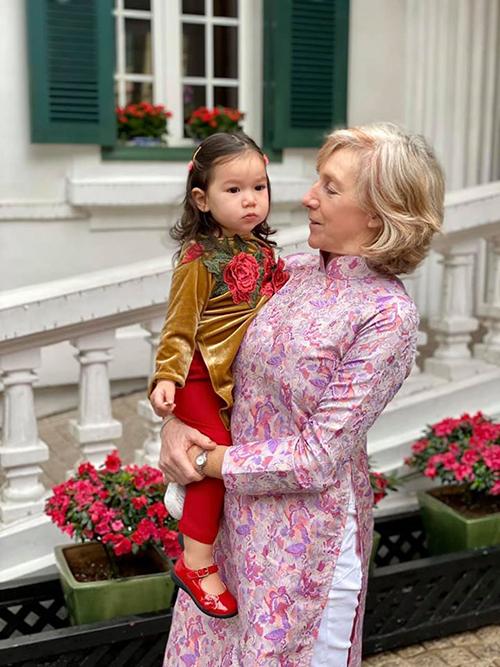 Mẹ chồng người ngoại quốc của siêu mẫu cũng xúng xính áo dài đồng điệu với cháu gái. Tuy nhiên, Myla vì mải ăn táo nên không chịu hợp tác khi cùng bà chụp ảnh.