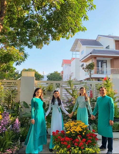 Gia đình MC Quyền Linh diện áo dài ton sur ton tạo dáng trong vườn nhà.