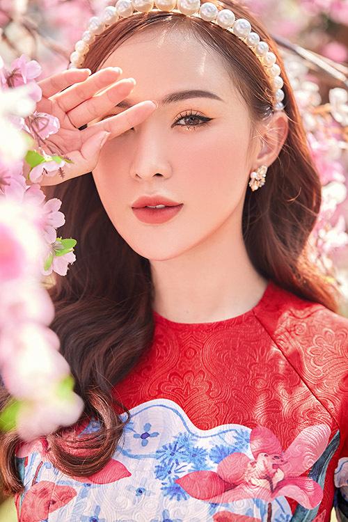 Kelly khoe sắc bên hoa đào trang trí ở một phim trường tại Sài Gòn.