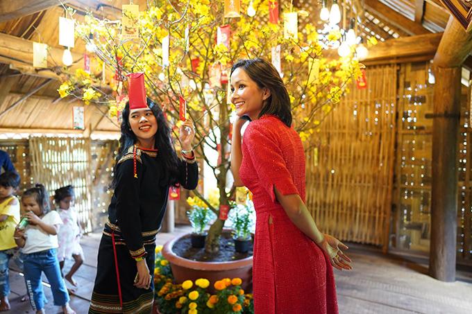 Người đẹp diện áo dài đỏ, mong muốn một năm sẽ nhiều điều may mắn. Cô vui vẻ chụp ảnh kỷ niệm cùng mọi người bên cây mai vàng.