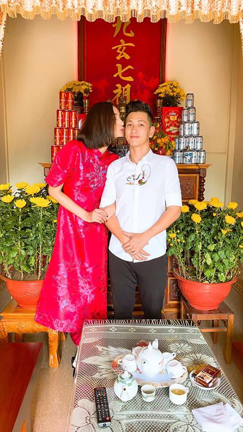 Cô diện áo dài đỏ và tình tứ hôn chồng trong phòng khách của gia đình.