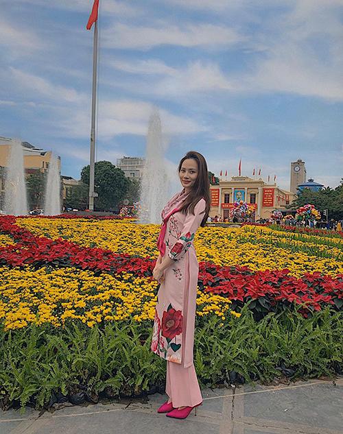 Nguyễn Diệu Linh chọn áo dài trang trí hoa lá khi dạo phố hoa ở Hải Phòng.