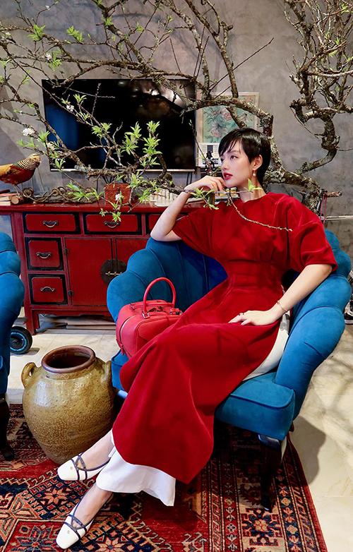 Trong ngày mưa gió đầu xuân ở Hà Nội, Khánh Linh chọn áo dài nhung đỏ tươi để mang lại sự ấm áp và hy vọng may mắn cả năm.