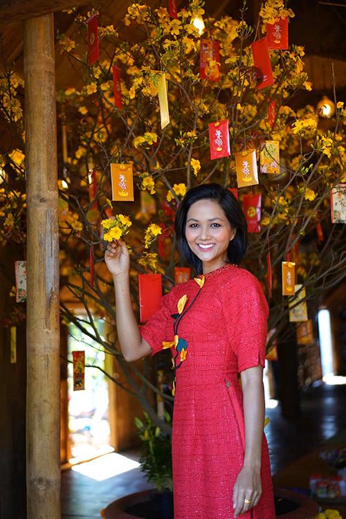 Đón Tết cùng gia đình tại Đăk Lăk, hoa hậu HHen Niê cũng chọn mẫu áo dài cách tân tông đỏ, trang trí hoa nổi để chưng diện.