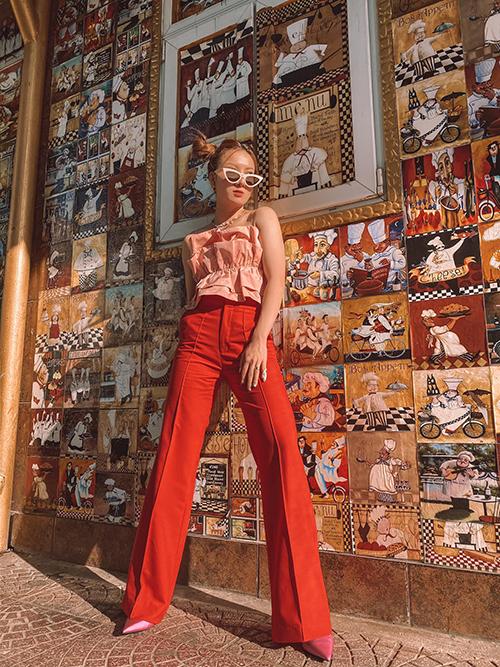 Yến Nhi tôn dáng với quần ống suông tông màu đỏ tươi. Trang phục đi kèm là áo quây trang trí bèo nhún điệu đà gam hồng thạch anh.