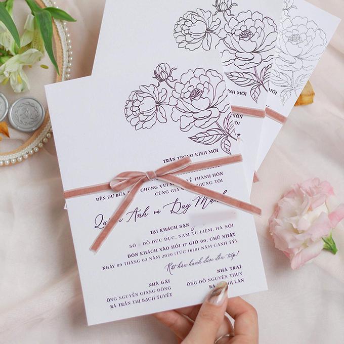 Lễ vu quy, tiệc cưới của Quỳnh Anh - Duy Mạnh đều diễn ra ngày 9/2 tại Hà Nội. Bộ thiệp mang xu hướng tối giản, chỉ sử dụng rất ít điểm nhấn là hoạ tiết hoa mẫu đơn ánh bạc, được niêm bởi ruy băng hồng.