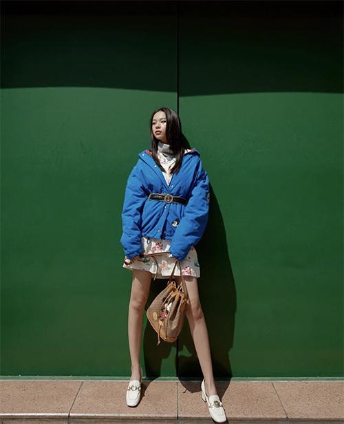Khi đi chơi Tết ở những vùng khí hậu mát lạnh, các nàng có thể tham khảo cách phối áo phao gam xanh blue cùng váy hoa của Phí Phương Anh.