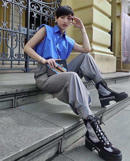 Set đồ của Khánh Linh dành cho các bạn gái thích thể hiện vẻ đẹp cá tính và trẻ trung khi đi chơi Tết. Sơ mi tông xanh đúng xu hướng 2020 được fashionista phối cùng quần âu ống thụng biến tấu độc đáo.