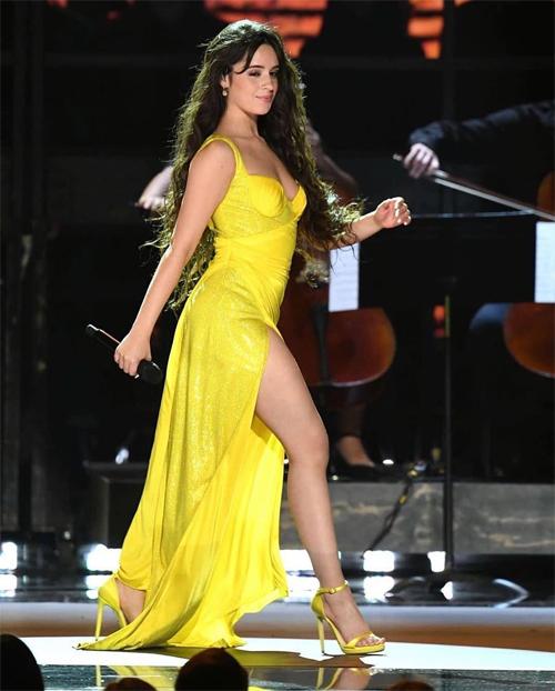 Nữ ca sĩ thay hai bộ đầm khác khi biểu diễn, trong đó có đầm vàng xẻ cao gợi cảm.