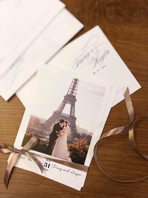 Mặt trước tấm thiệp cưới được thiết kế đơn giản với hình cưới của uyên ương được chụp ở Pháp, tô điểm bởi chiếc ruy băng màu nâu. Xu hướng thiệp in ảnh cưới uyên ương đã xuất hiện từ lâu và vẫn là hot trend, giúp khách mời nhận biết cô dâu, chú rể dễ dàng trong tiệc cưới.Thiệp cưới được thiết kế với tông màu chủ đạo nâu - trắng mang phong cách châu Âu.