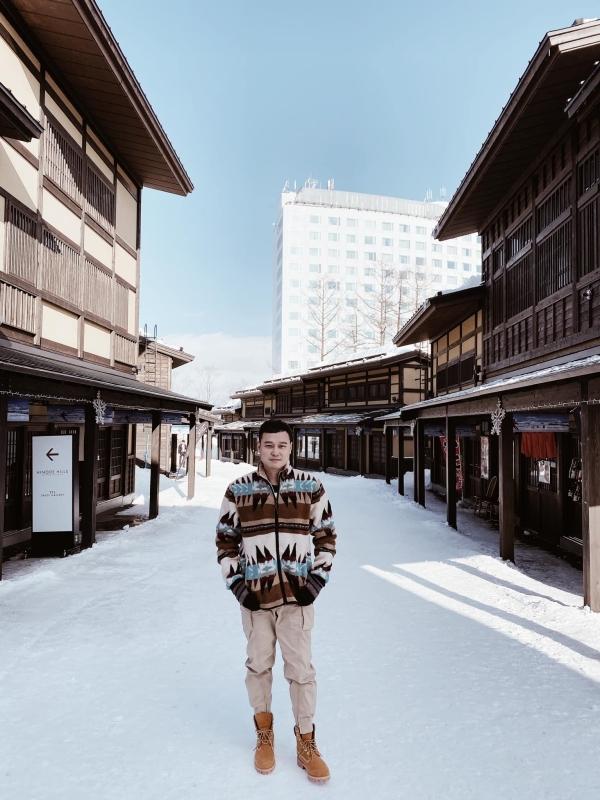 Quang Vinh cũng check-in Hilton Niseko ngay thời điểm này. Tòa nhà màu trắng sau lưng hoàng tử sơn ca là trạm cáp treo đưa kháchlên núi trượt tuyết vào mùa đông, hay đơn giản chỉ là đi ngắm cảnh vào mùa xuân, hè, thu... Dưới chân núi là ngôi làng nhỏ với các tòa nhà xây bằng gỗ mang nét cổ kính.