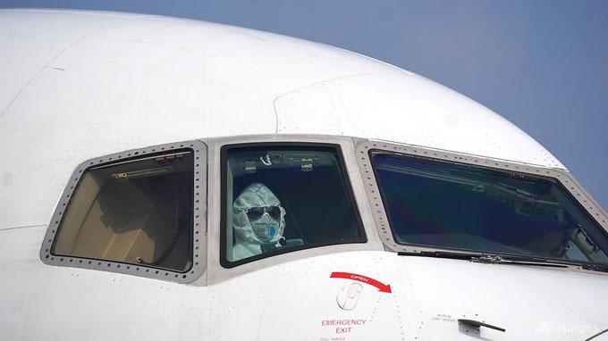 Phi công mặc bộ đồ bảo hộ kín mít từ đầu tới chân khi đỗ chiếc máy bay chở hàng tại sân bay Quốc tế Tianhe ở thành phố Vũ Hán.