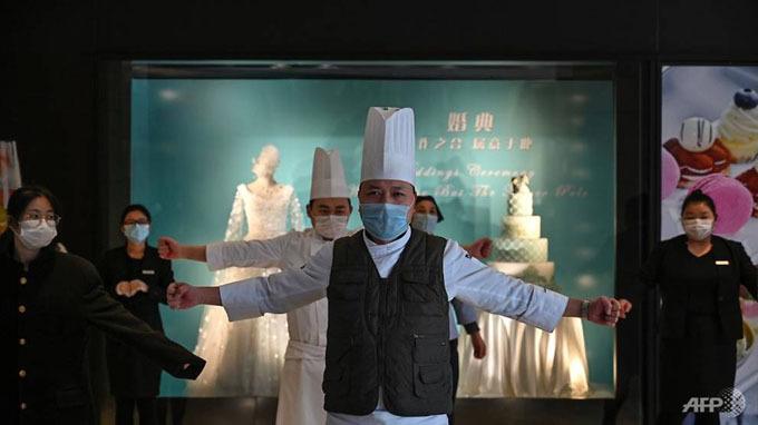 Các nhân viên tại một khách sạn ở Vũ Hán vừa đeo khẩu trang vừa thực hiện vài động tác khởi độngtrong giờ họp giao ban trước khi bắt đầu ngày làm việc.