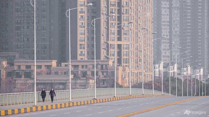 Vài người hiếm hoi đi bộ trên đường, không quên đeo khẩu trang.