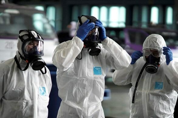 Các nhân viên của Thai Airway mặc đồ bảo hộ trước khi làm công tác khử trùng một máy bay của hãng này tại sân bay Suvarnabhumi - Ảnh: REUTERS