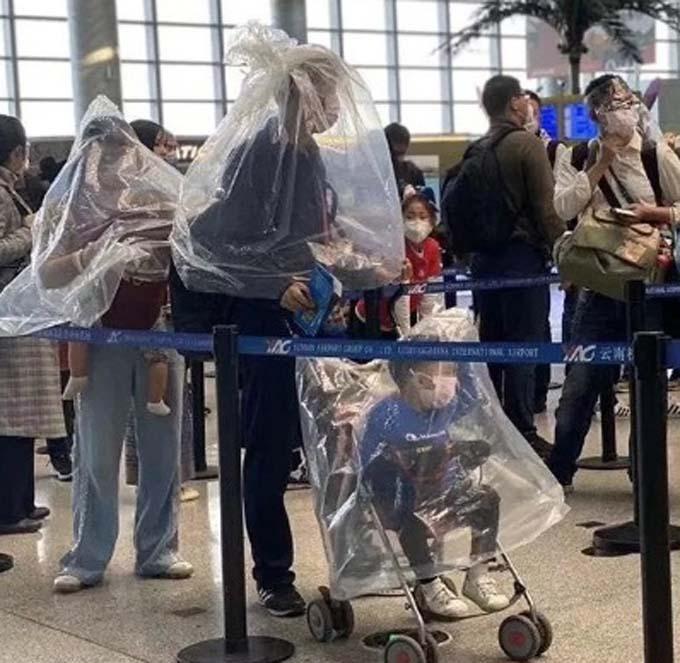 Một gia đình khác thì trùm túi ni lông kín mít quanh người khi đang đứng xếp hàng ở sân bay, toàn bộ thành viên trong nhà cũng không quên đeo khẩu trang.