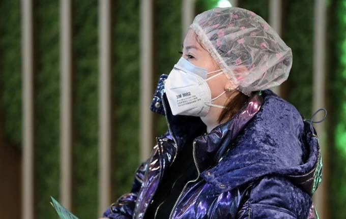 Người phụ nữ này thì đeo hai lớp khẩu trang và mũ trùm đầu. Ảnh: Reuters.