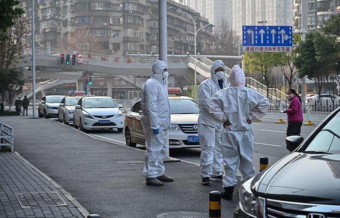 Cảnh sát và nhân viên y tế phải mặc đồ bảo hộ để di chuyển xác của người đàn ông chết trên vỉa hè Vũ Hán hôm 30/1. Ảnh: AFP.